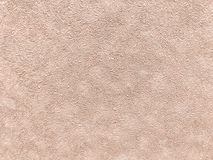 Texture of light beige wallpaper with a pattern. Texture of light brown wallpaper with a curly pattern. Coral paper surface, structure close-up Stock Image