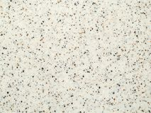 Texture light gray artificial stone with black and brown crumbs. Background royalty free stock photo