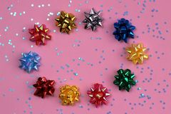 The texture of a lot of festive bows in the form of a star on a pink background in the shape of an oval. Bow, background picture, banner, birthday, celebration stock photography