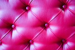 Texture of a luxurious, bright, beautiful, pink, stitched leather sofa with rivets, buttons, backdrop. Background Royalty Free Stock Images