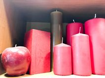 Texture of many festive different forms of red, burgundy wax candles with wicks standing in a row. The background stock photography