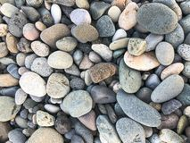 Texture of many multicolored beautiful round and oval smooth natural stones, pebbles. The background.  stock photos