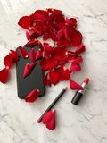 Smartphone in iphone style black color with red rose petals and red lipstick on marble tabletop background, top view royalty free stock photos