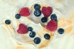 The texture of the meringue cake with blueberries and raspberries. Texture of the meringue cake with blueberries and raspberries Stock Image