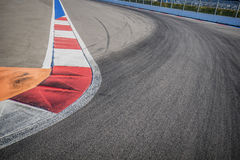 Texture of motor race asphalt and red white curb. Close up on Grand Prix street circuit Royalty Free Stock Images