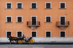 Texture of multistory house wall with balconies and windows. Palma de Mallorca, Spain - May 27, 2016: Horse-drawn carriage in front of texture of multistorey Stock Photo
