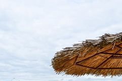Texture of a natural straw dry beach sun umbrella made from hay dried grass and branches on the beach against a blue sky at stock photos