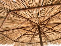 Texture of a natural straw dry beach sun umbrella made from hay dried grass and branches on the beach against a blue sky at royalty free stock photo