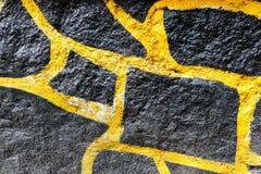 Texture noire et jaune de mur de roche Image libre de droits