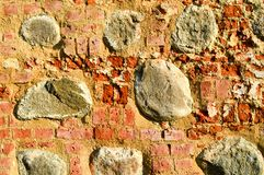 The texture of the old ancient medieval antique stone hard peeling cracked brick wall of rectangular red clay bricks and large. Stones, cobblestones. The stock images