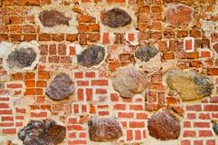 The texture of the old ancient medieval antique stone hard peeling cracked brick wall of rectangular red clay bricks and large. Stones, cobblestones. The royalty free stock images