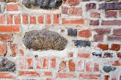 The texture of the old ancient medieval antique stone hard peeling cracked brick wall of rectangular red clay bricks and large. Stones, cobblestones. The stock image