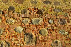 The texture of the old ancient medieval antique stone hard peeling cracked brick wall of rectangular red clay bricks and large. Stones, cobblestones. The royalty free stock photos