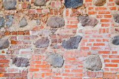 The texture of the old ancient medieval antique stone hard peeling cracked brick wall of rectangular red clay bricks and large. Stones, cobblestones. The stock photos