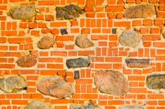 The texture of the old ancient medieval antique stone hard peeling cracked brick wall of rectangular red clay bricks and large. Stones, cobblestones. The stock photo