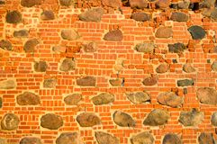 The texture of the old ancient medieval antique stone hard peeling cracked brick wall of rectangular red clay bricks and large. Stones, cobblestones. The royalty free stock photography