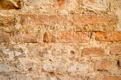 The texture of the old ancient medieval antique sturdy stone peeling scratched wall of rectangular red orange bright brick. With seams and cracks. The royalty free stock image