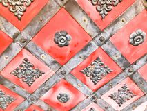 Texture of an old ancient medieval red antique sturdy iron metal door with rivets and nails patterns. The background.  stock photos