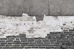 Texture of an old black brick wall with destroyed plaster Stock Image