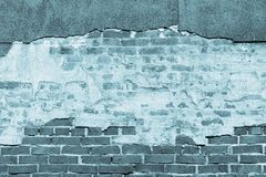 Texture of an old blue brick wall with destroyed plaster Royalty Free Stock Images
