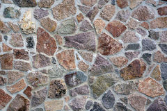 Texture Old brick or stone wall made of cobblestones background. Stock Image
