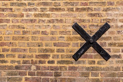 Texture of old brick wall with a black metal cross on it Royalty Free Stock Photography