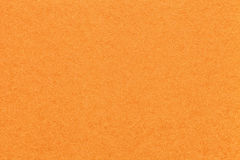 Texture of old bright orange paper background, closeup. Structure of dense carrot cardboard stock image
