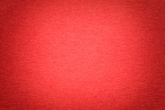 Texture of old bright red paper background, closeup. Structure of dense cardboard. Texture of vintage dark red paper background with vignette. Structure of dense stock image