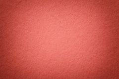 Texture of old bright red paper background, closeup. Structure of dense cardboard. Texture of vintage dark red paper background with vignette. Structure of dense stock photography