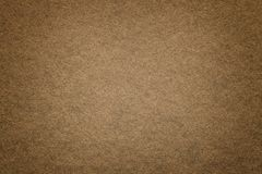 Texture of old dark brown paper background, closeup. Structure of dense cardboard. Texture of vintage dark brown paper background with vignette. Structure of stock image