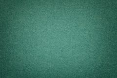 Texture of old dark green paper background, closeup. Structure of dense emerald cardboard. Texture of vintage dark green paper background with vignette stock images