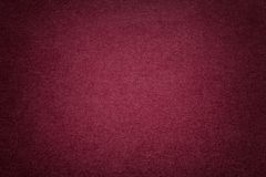 Texture of old dark red paper background, closeup. Structure of dense cardboard. Texture of vintage dark red paper background with vignette. Structure of dense stock photography