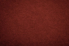 Texture of old dark red paper background, closeup. Structure of dense maroon cardboard.  stock photo