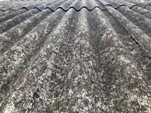 Texture of old dilapidated bulk gray slate, sloping roof of asbestos located vertically covered with green moss. Background Royalty Free Stock Photos