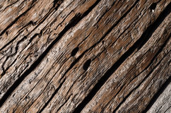 The texture is an old gray, rotted wooden board with deep wavy cracks and holes. Horizontal photo, wallpaper Stock Photo