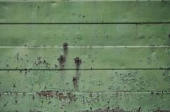 Texture of an old green metal wall with significant damage from exposure to unfavorable weather conditions and dampnes. S royalty free stock photography