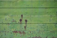 Texture of an old green metal wall with significant damage from exposure to unfavorable weather conditions and dampnes. S stock photography