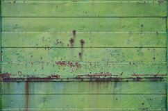 Texture of an old green metal wall with significant damage from exposure to unfavorable weather conditions and dampnes. S royalty free stock images
