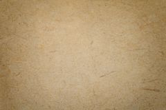 Texture of old light brown paper background, closeup. Structure of dense cardboard. Texture of vintage dark brown paper background with vignette. Structure of royalty free stock photo