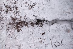 The texture of the old concrete wall is covered with cracks and stains of mold, shabby background. Grunge Style Wallpaper royalty free stock photo