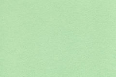 Texture of old light green paper closeup. Structure of a dense cardboard. The mint background. royalty free stock photos