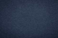 Texture of old navy blue paper background, closeup. Structure of dense dark denim cardboard Stock Photos
