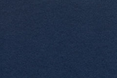 Texture of old navy blue paper closeup. Structure of a dense cardboard. The denim background. Texture of old dark navy blue paper closeup. Structure of a dense stock photo