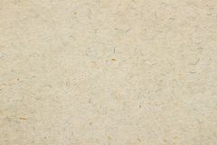 Texture of old organic light cream paper. Recyclable material with small brown and and blue inclusions of cellulose royalty free stock photo