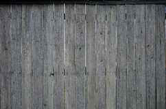The texture of an old rustic wooden fence made of flat processed. Boards. Detailed image of a street fence of a rustic type made of wooden material close-up Royalty Free Stock Photos