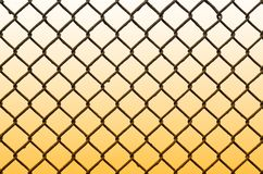 Texture of an old and rusty metal mesh on a neutral colored back. Ground. A sad and gloomy image with a flat fencing net used in prisons or industrial plants stock image