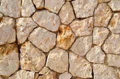 Texture of an old stone yellow wall from uneven different ancient friable stones of different shapes with sandy seams. The backgro royalty free stock photos