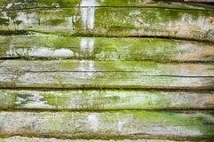The texture of the old wooded wall of logs thrown by green moss, a fence of horizontal, dilapidated rotten boards of different siz. Es with cracks and knots Stock Photo