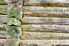 The texture of the old wooded wall of logs thrown by green moss, a fence of horizontal, dilapidated rotten boards of different siz. Es with cracks and knots Royalty Free Stock Image