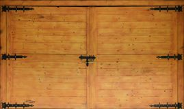 The texture of old wooden gates, old made of yellow treated wood with metal black door hinge. S stock image